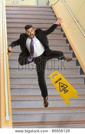 Mature Hispanic businessman falling on stairs