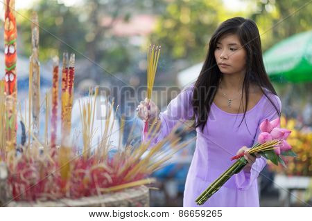 Vietnamese woman inserting incense stick in giant burner praying at temple