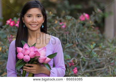 Asian woman with lotus flowers bud posing in front of a desert rose tree