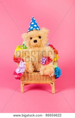 Stuffed birthday bear with present in chair on pink background