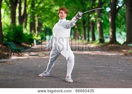 Young beautiful rapier fencer woman staying in park alley ready for competition