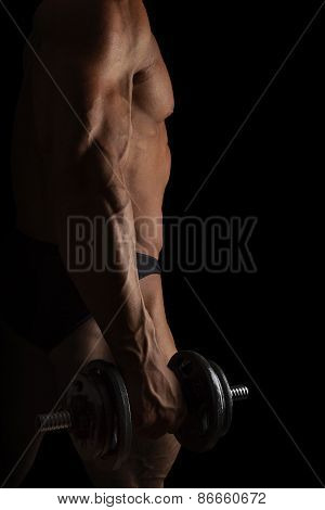 Sport And Fitness. Sexy Bodybuilder Holding Dumbbell Isolated On Black Background.