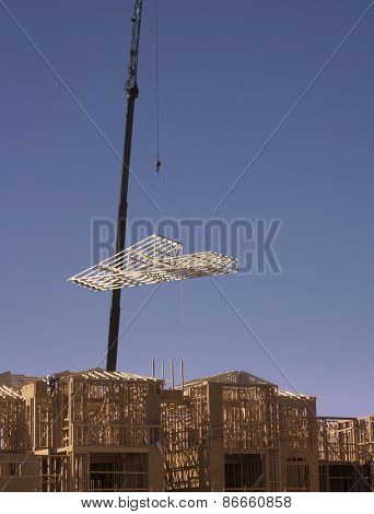 Crane lifting wood roof timber onto new construction site