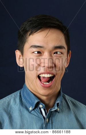 Funny young Asian man showing his tongue and making face