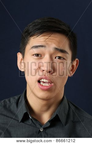 Young Asian man speaking and looking at camera