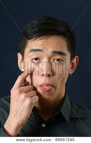 Young Asian man showing his eyelid and tongue