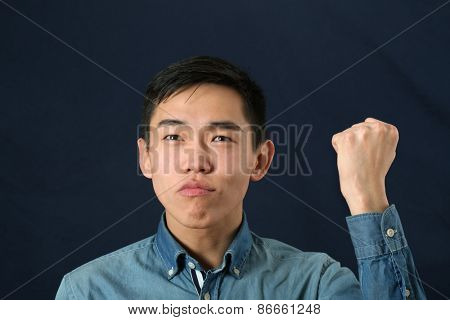 Funny young Asian man shaking his fist and looking upward