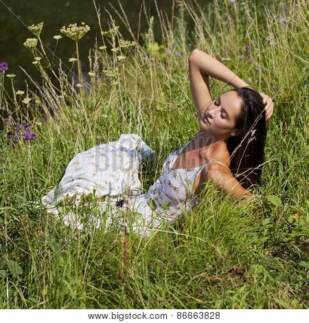Sexy woman in white long dress sitting on green grass