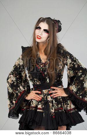 Beautiful young woman in  kimono dress on gray background