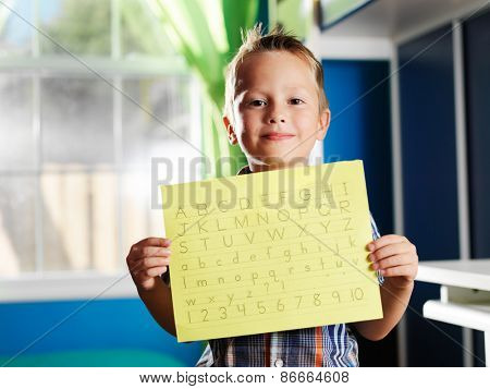 little boy holding completed homework
