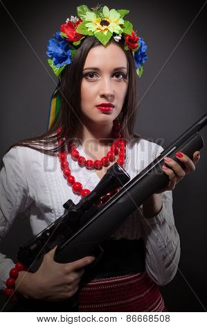 Beautiful Young Woman Wearing National Ukrainian Clothes And Holding A Rifle