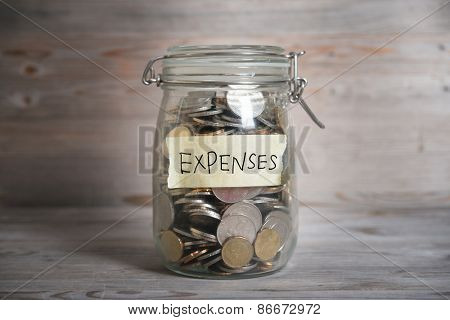Coins in glass money jar with expenses label, financial concept. Vintage wooden background with dramatic light.