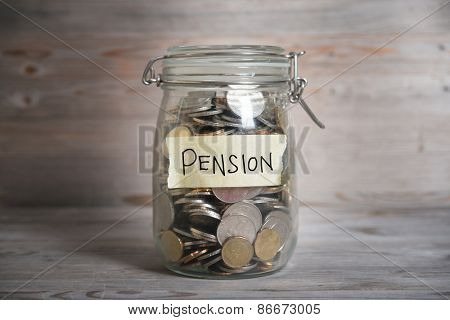 Coins in glass money jar with pension label, financial concept. Vintage wooden background with dramatic light.