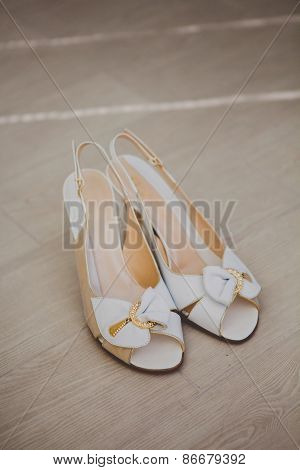 White wedding shoes with a bow on wood background