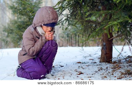 Sad freezing girl trying to stay warm in winter forest