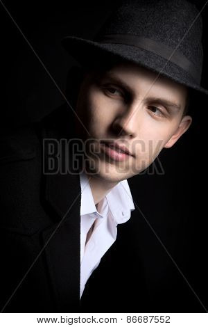 Low Key Shot Of Young Man In Hat