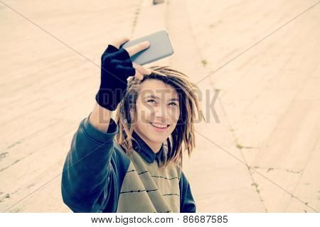 Guy Smiling Taking Selfie In The City Warm Filter Applied