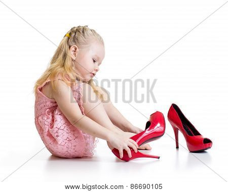 Little girl trying mother shoes on