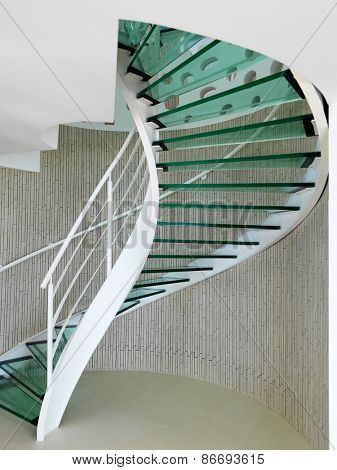 modern glass spiral staircase with metallic hand-rails.