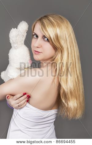 Caucasian Blond Woman Posing With Plush Rabbit Toy In Studio Against Gray Background