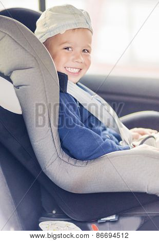 Portrait Of Young Caucasian Happy Little Boy Sitting On A Car Safety Seat Chair