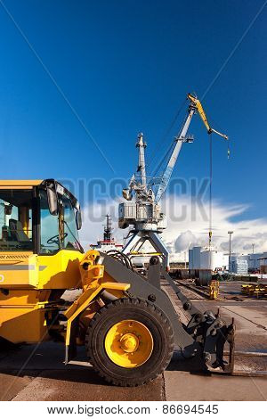 Yellow Forklift And Crane At Loading And Unloading Of Cargo In The Port
