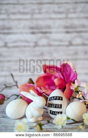 Small White Rabbit Figurine with Easter Eggs Surrounded by Pink Blossoms on Rustic Wooden Background with Copy Space Above