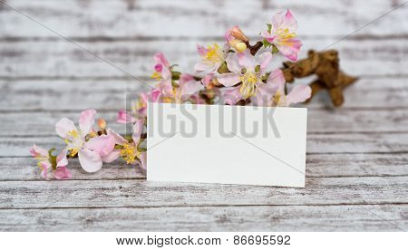 Empty White Note Paper with Fresh White and Pink Cymbidium Orchid Flowers on a Wooden Table.