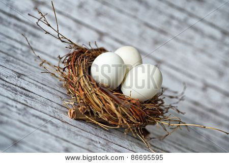 Close up Three White Chicken Eggs in a Nest on a Wooden Table in a Diagonal Shot