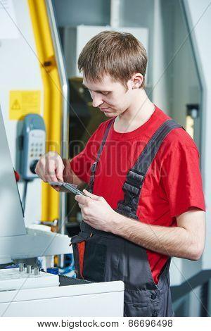 manufacture worker measuring detail at factory metal machining shop