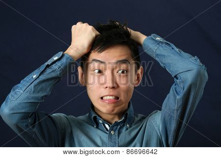 Disappointed young Asian man making face and looking sideways