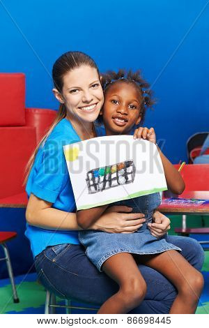 Girl and nursery teacher showing water color painting in kindergarten
