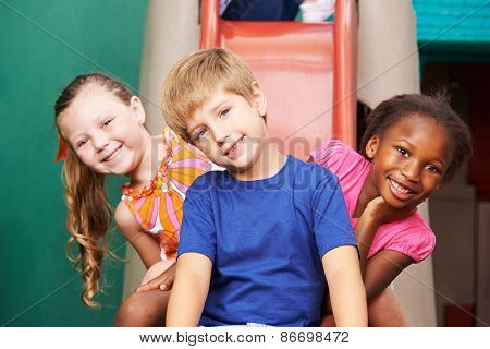 Three happy kids sitting on a slide in kindergarten
