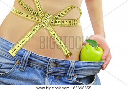 Woman's fit belly with measuring tape,apple and oversized jeans, isolated on white