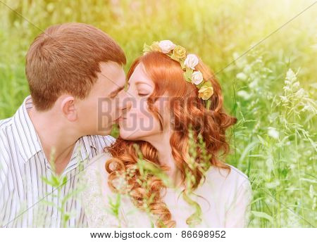 Closeup portrait of beautiful young couple kissing outdoors, spending wedding day in the park, sunny day, love and romance concept