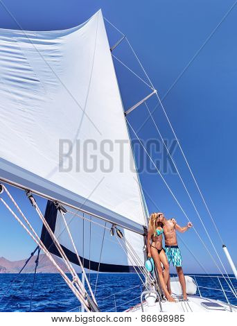 Happy couple in honeymoon vacation in luxury sea cruise, enjoying each other and travel on beautiful sailboat