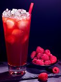 picture of cocktail  - Red raspberry drink  with ice cube and plate of berry on black background - JPG