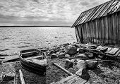 pic of old boat  - Old wooden fishing boat and barn on lake coast in Karelia - JPG