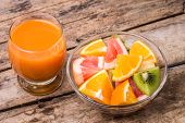 stock photo of fruit-juice  - Fresh fruit salad with glass of apple and carrot juice on old wooden table - JPG