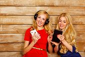 image of sisters  - Two sisters blonde listening to music on headphones - JPG