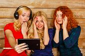 picture of three sisters  - Three sisters blond and red listening to music on headphones - JPG