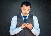 image of jaw drop  - Closeup portrait funny young man in vest and blue tie shocked surprised wide open mouth by what he sees on his cell phone isolated gray black background - JPG