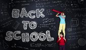 picture of frot  - Cute boy and girl learning playfully in frot of a big blackboard - JPG