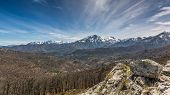 foto of wispy  - View of snow covered Monte Pardu and San Parteo in the Balagne region of north Corsica with rocks trees and maquis in the foreground and blue skies and wispy clouds - JPG