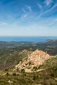 image of wispy  - The mountain village of Speloncato in the Balagne region of north Corsica with maquis and the Mediterranean in the background against a blue sky and wispy clouds - JPG