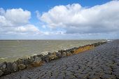 stock photo of dike  - Storm raging over a lake along a dike through Flevoland in spring - JPG