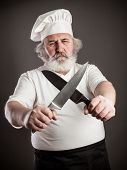 stock photo of chef knife  - Grumpy old chef with two knives against dark background - JPG