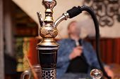 stock photo of shisha  - Person smoking nargile in the asian restaurant - JPG