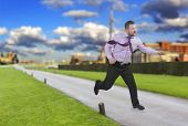 foto of running-late  - Running businessman in a hurry and modern city in background - JPG