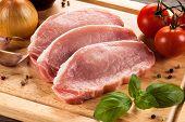 image of pork chop  - Raw pork chops on cutting board and vegetables - JPG